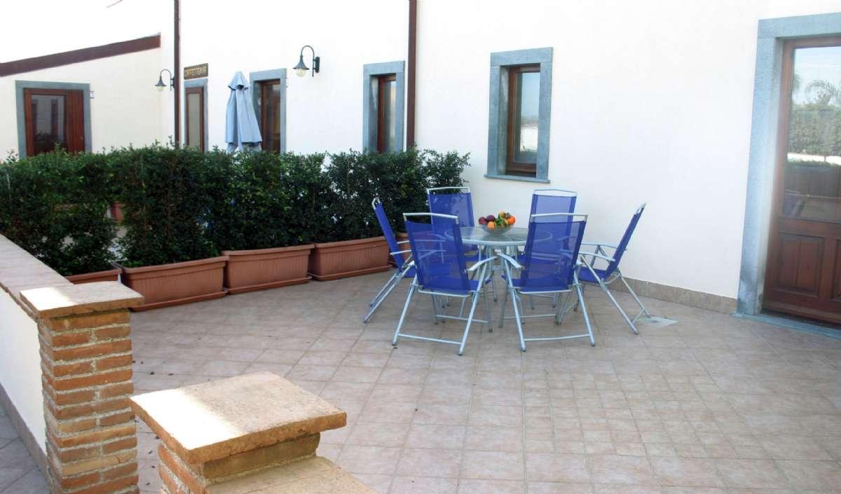 Udendørs arealer med bord og stole i stueetagen