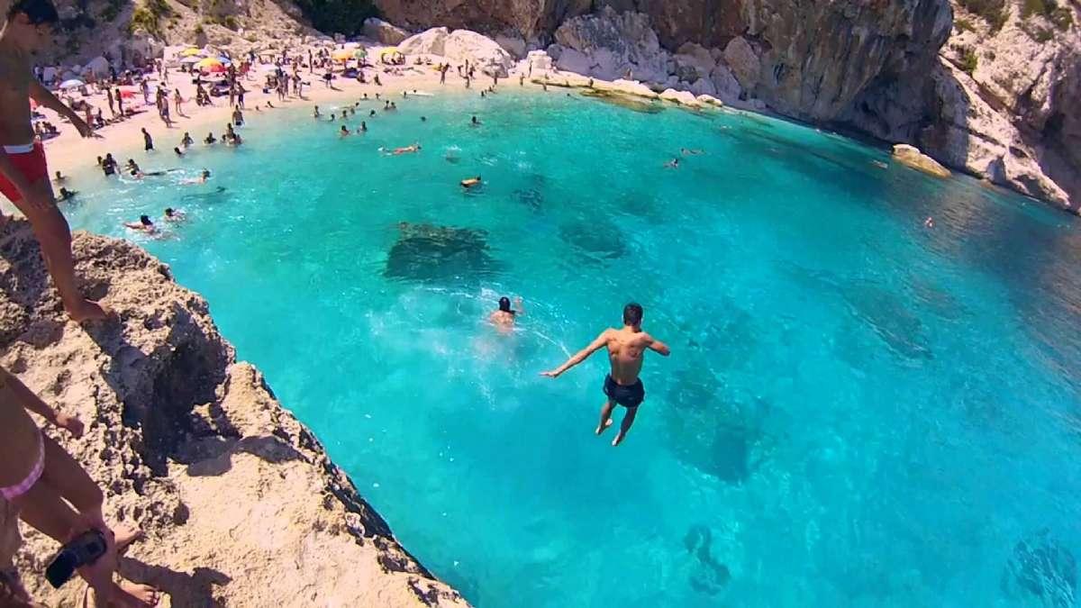 Hop i vandet i det azurblå havvand under Ogliastra klipper