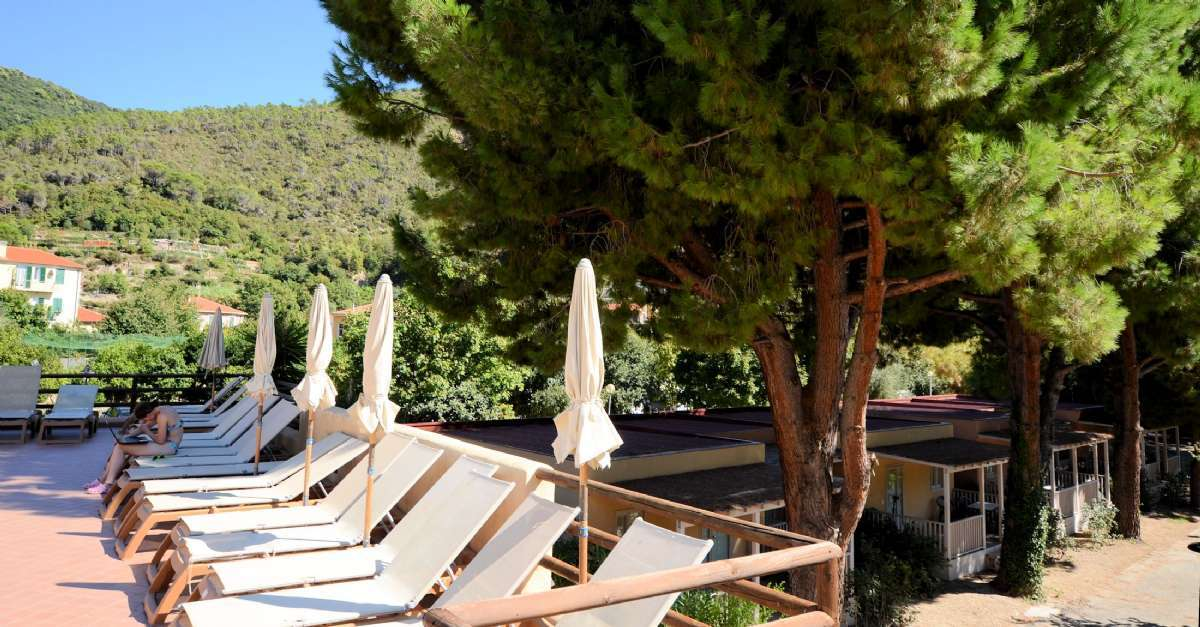 Her ser I terrassen ved poolen og i baggrunden bungalow-rækkehusene Villino