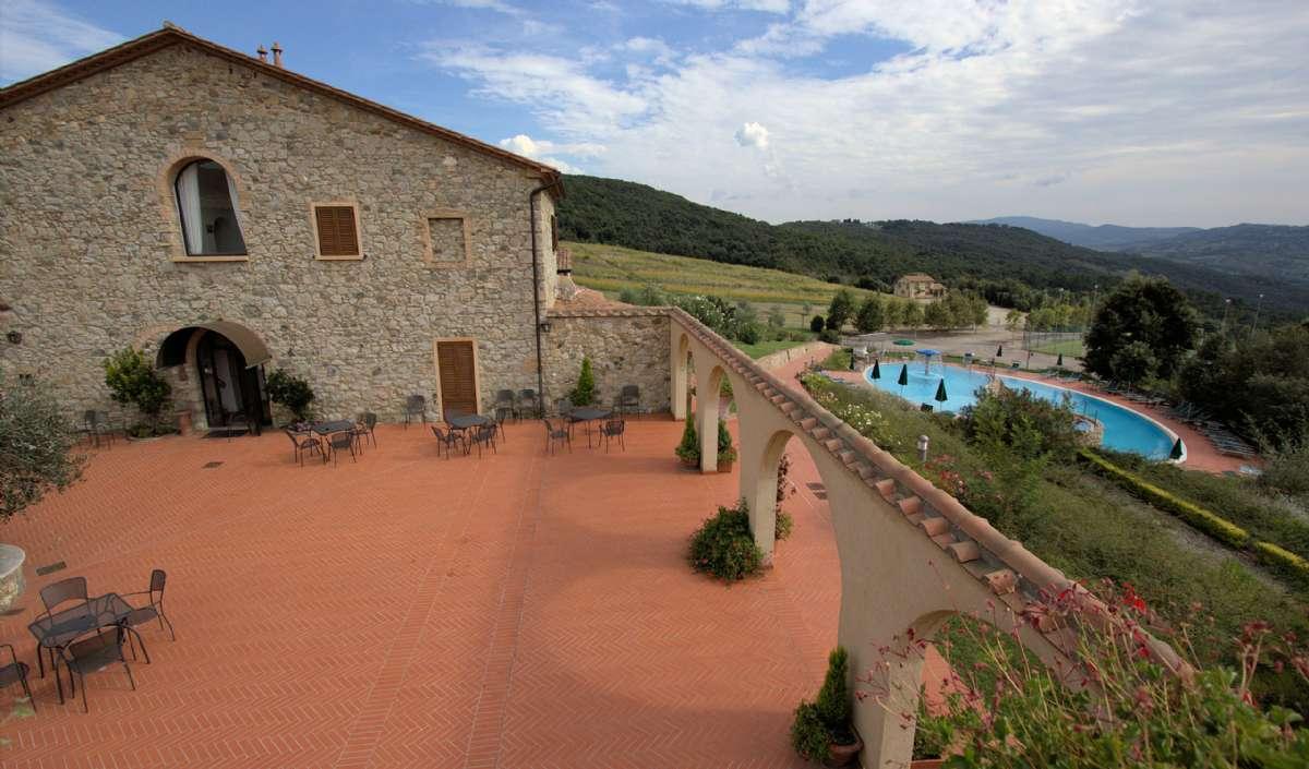 Le Tegoles gode restaurant samt pool og La Casina di Caccia i baggrunden