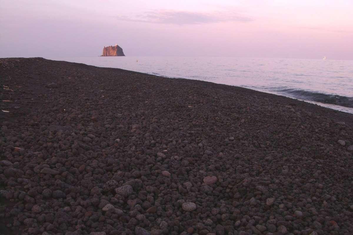 Strombolicchio i kvälls skymningen sedd från Strombolis svarta strand