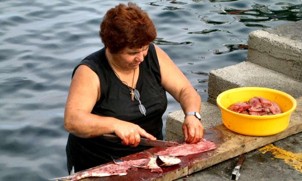 Die Frau des Fischers bereitet den Fang des Tages vor