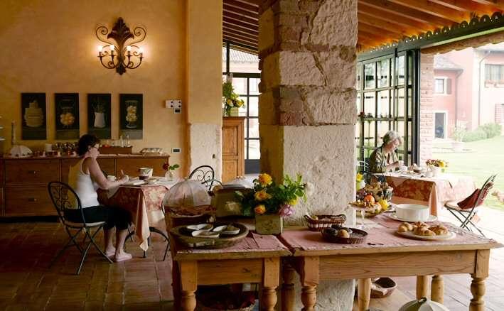 La salle de petit-déjeuner avec vue sur les oliviers de la ferme