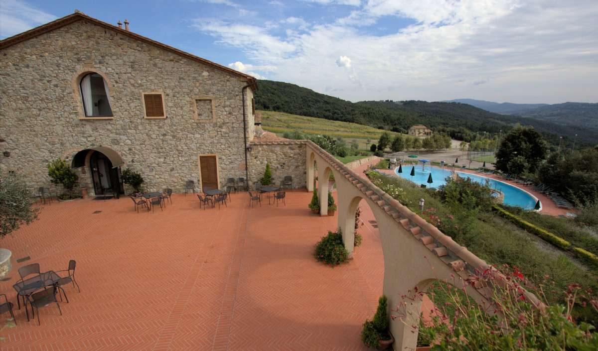 The restaurant at Le Tegole as well as the pool and La Casina di Caccia in the background