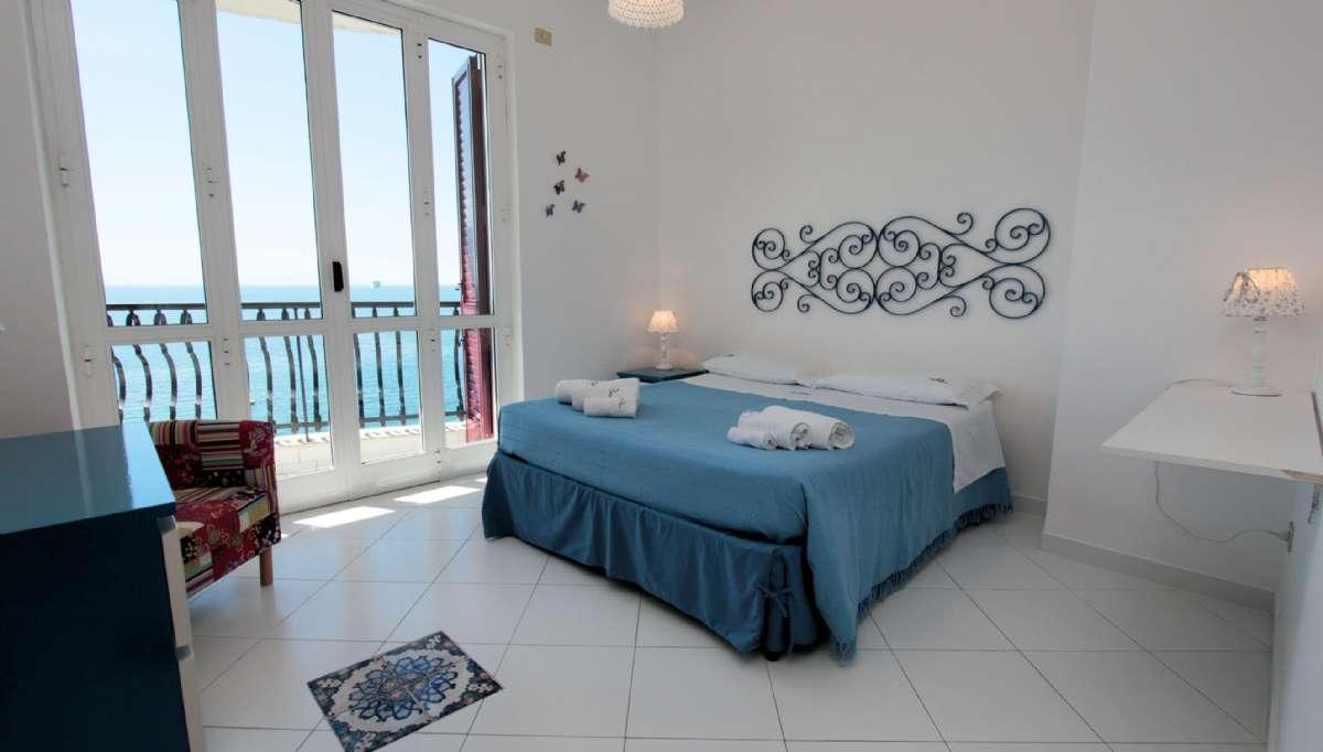 Soveværelset med udgang til terrasse og havudsigt i toværelseslejligheden
