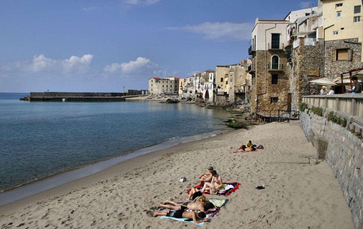 Stranden med utsikt mot den gamla stadsdelen och hamnen