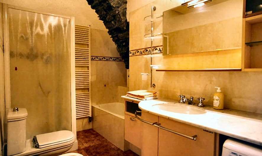 Rummeligt badeværelse med bruser og vaskemaskine