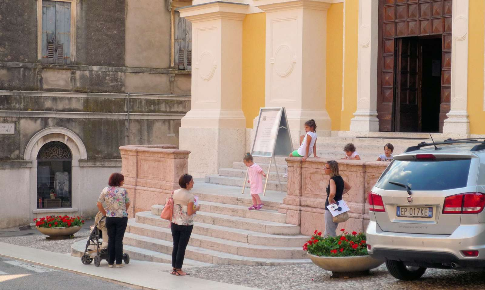 Children and their mothers stop for a chat and a little play on the town's church stairs on the way home from school and kindergarten